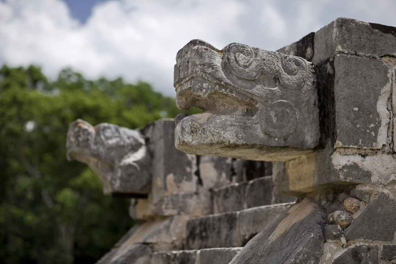Several snake heads protruding from the side of a Mayan ruin.