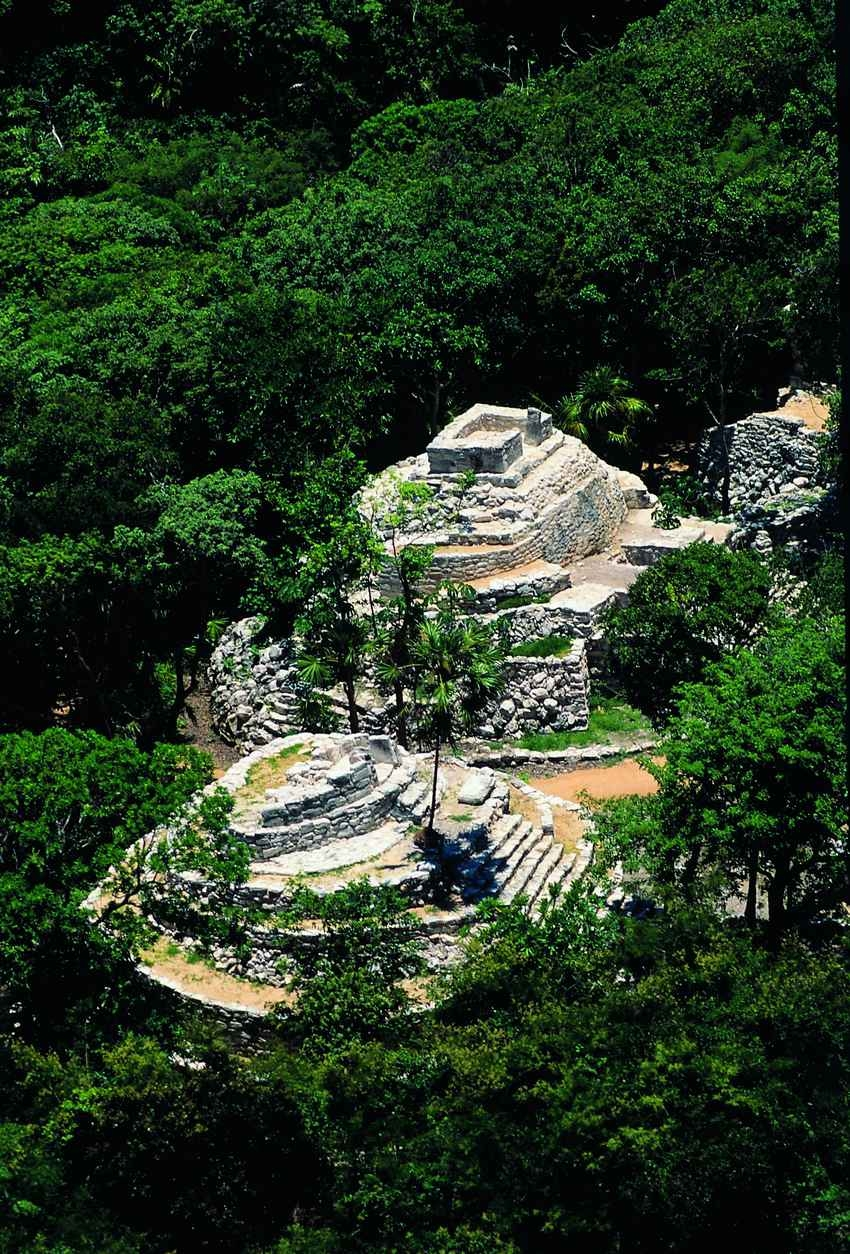 An aerial view of several Mayan pyramids in the middle of the jungle.