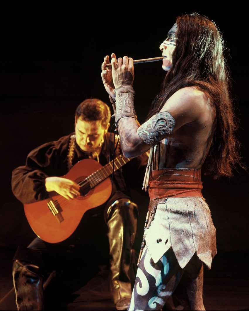 A Mayan warrior playing the flute and another man playing the guitar.