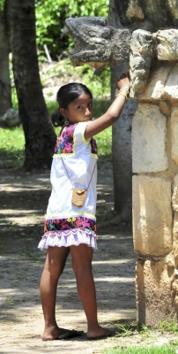 A young Mayan girl near some Mayan ruins in the jungle.