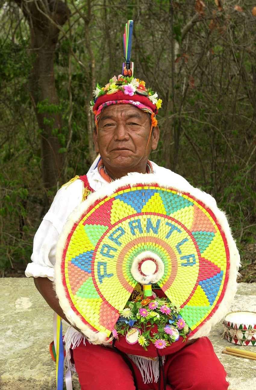 An elderly Mayan man in full regalia.