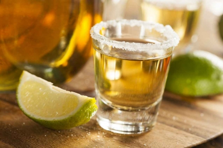 A tequila shot with salt around the rim and limes on its sides.