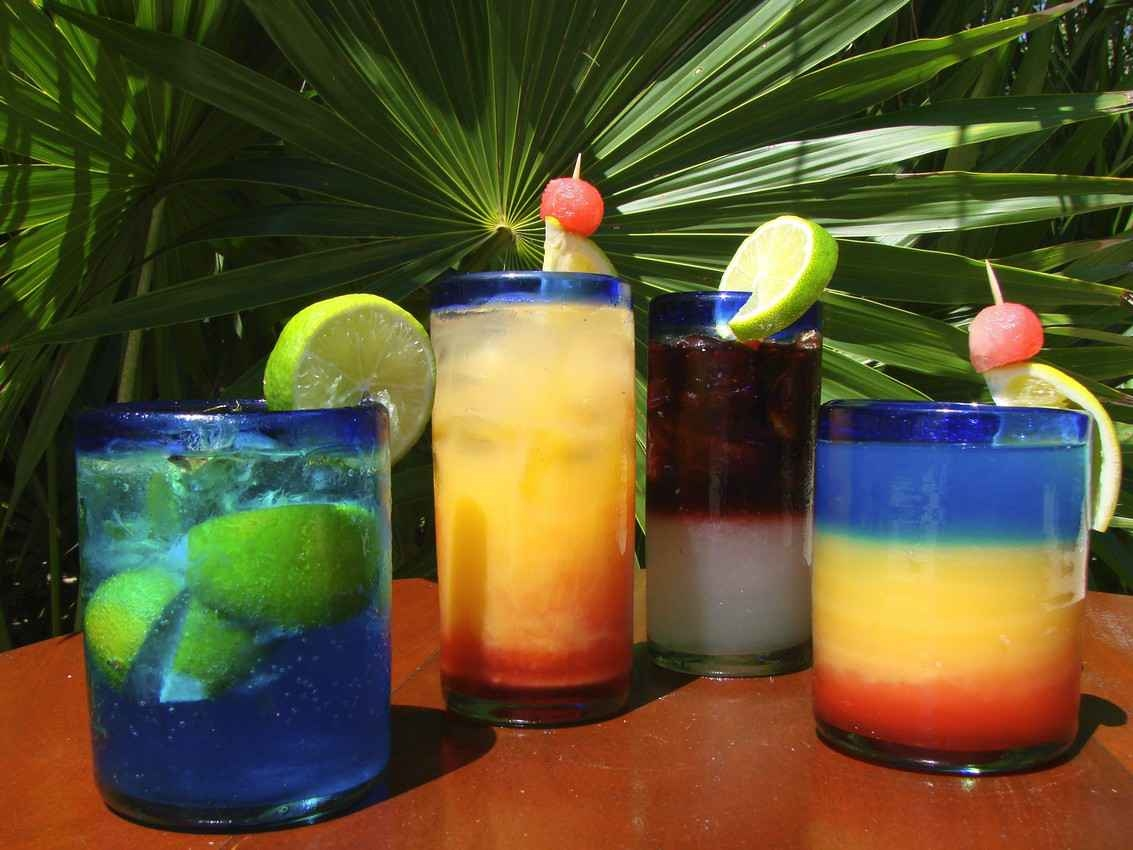 Several cocktails on a table with a jungle in the background.