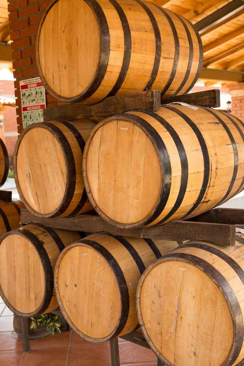 Several barrels filled with aging tequila at a tequila manufacturing plant.