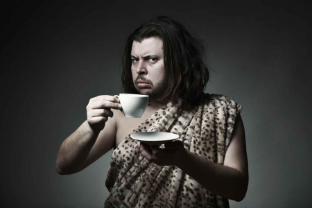 A caveman drinking tea from a cup and saucer.