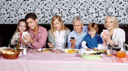 A family eating lunch with everyone talking privately on their phones.
