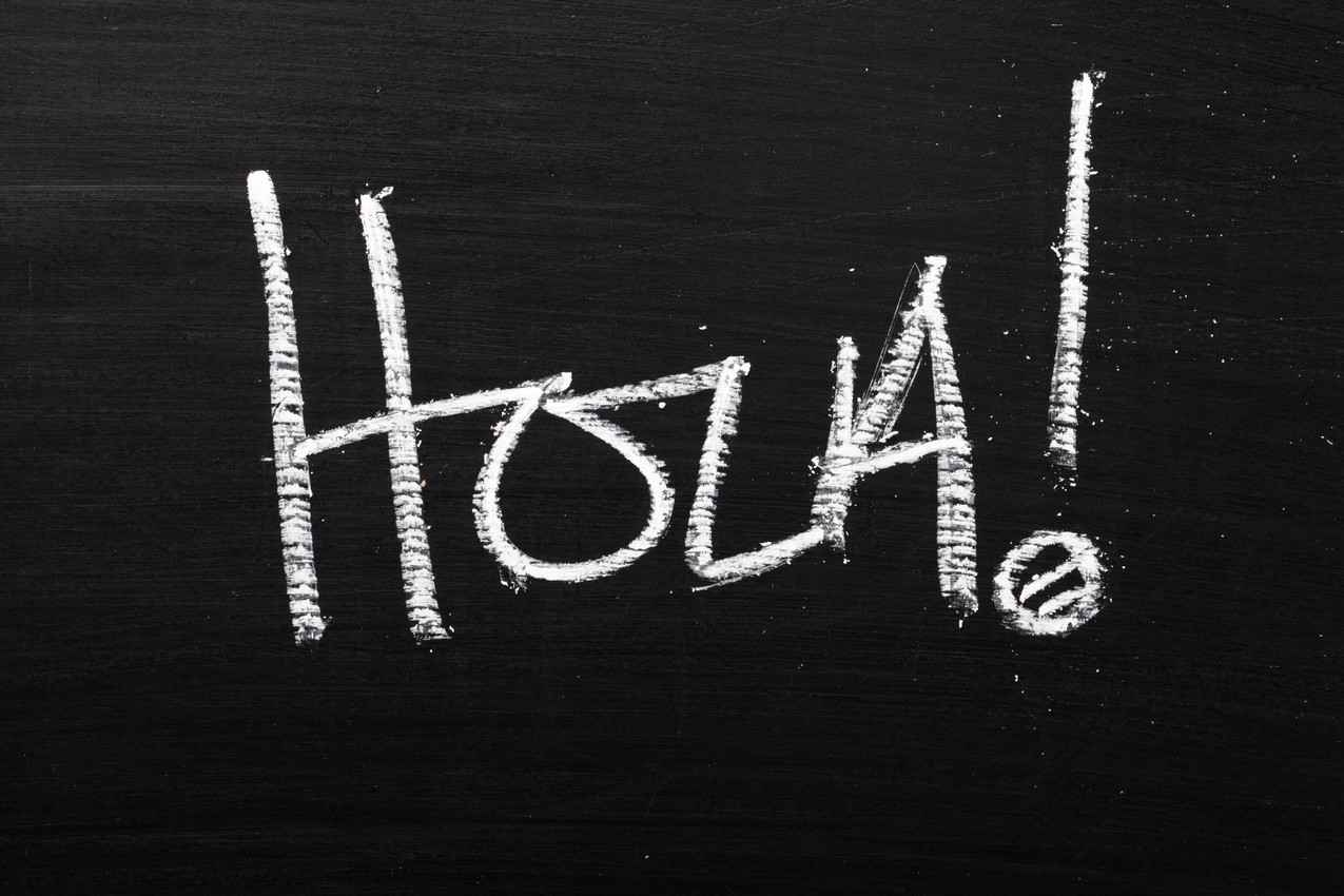 Hola written on a chalkboard.