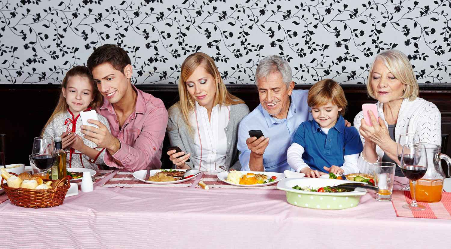 A Family Eating Lunch With Everyone Talking Privately On Their Phones