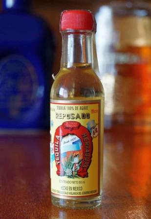 A miniature bottle of Reposado tequila.