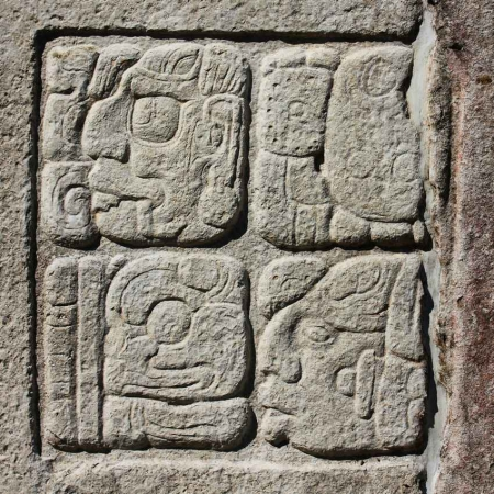 Mayan art on the side of a rock formation.