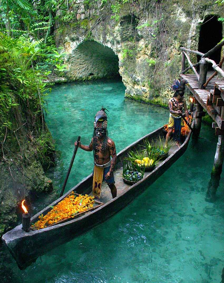 Several Mayan warriors riding a canoe on the hidden River near Playa Del Carmen.