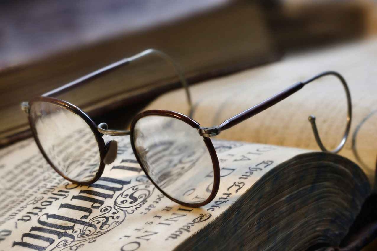 A pair of classical reading glasses on top of an ancient textbook.
