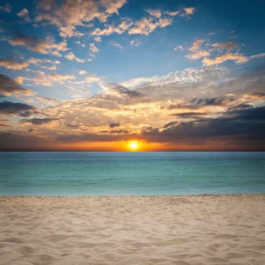 A great sunrise with orange clouds above the beach and clear blue water with white sand.