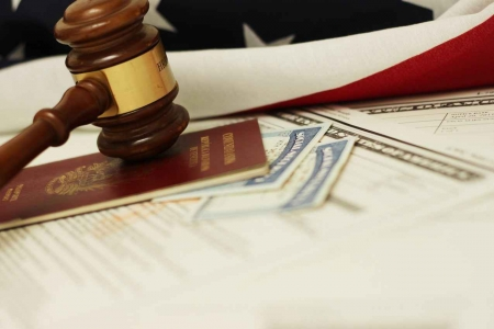 A passport with two Social Security cards and a judge's gavel near a US flag.