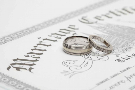 A male and female wedding ring on top of a marriage certificate.