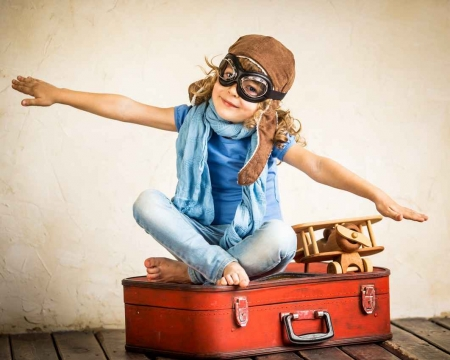 A little girl sitting on a suitcase pretending that she is flying.