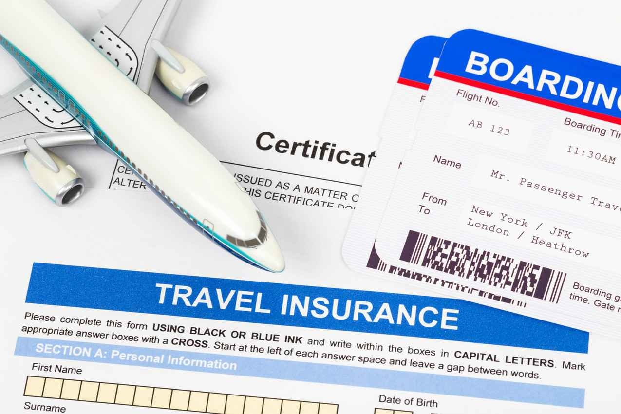 A travel insurance form with a boarding pass and model jet on top of it.