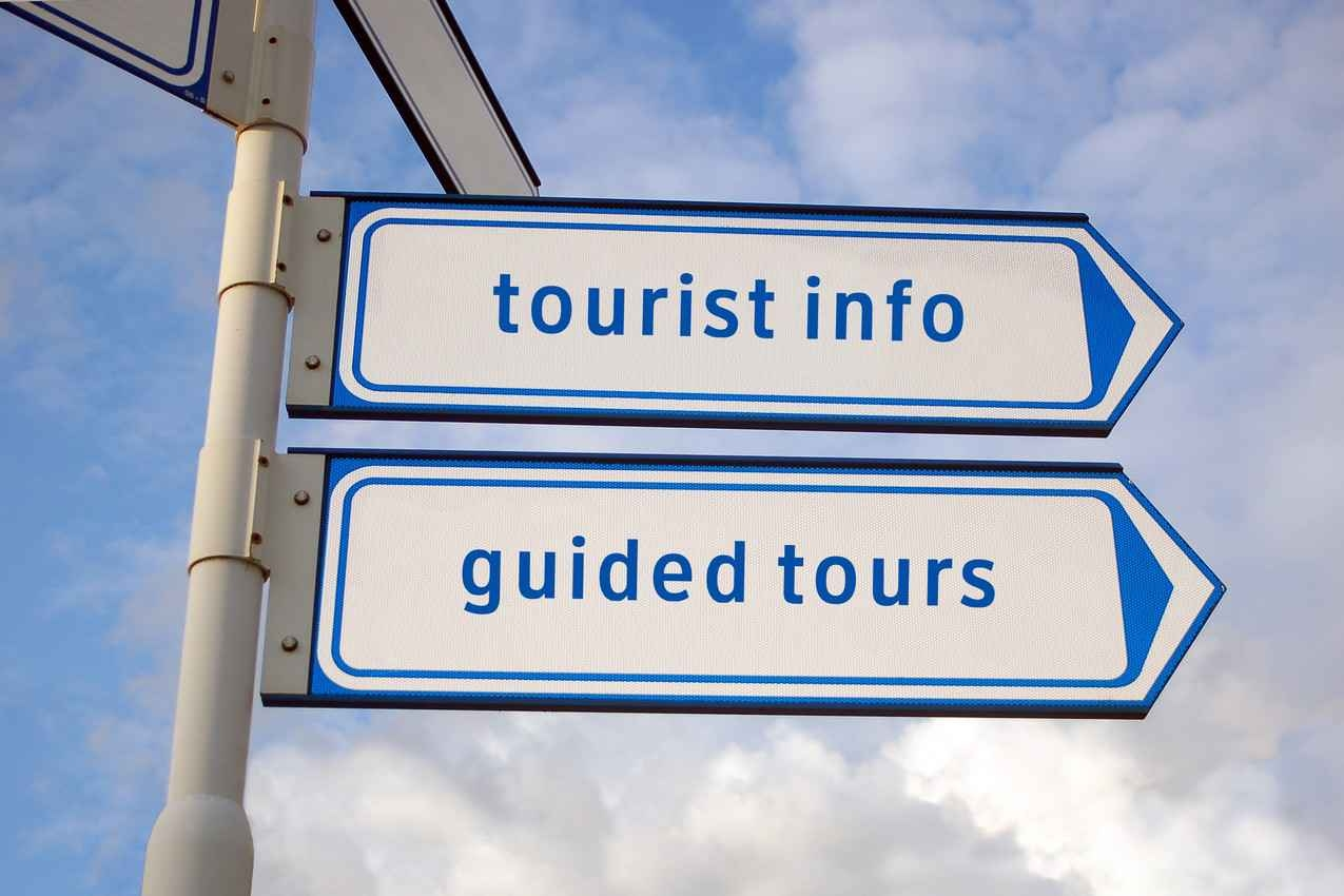 A sign post that says tourist info and guided tours.