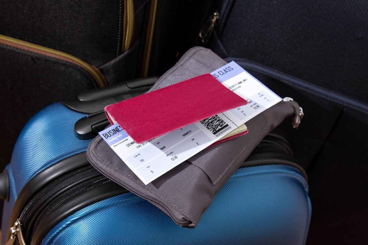 A suitcase next to an auxiliary bag, a diary, and a plane ticket.