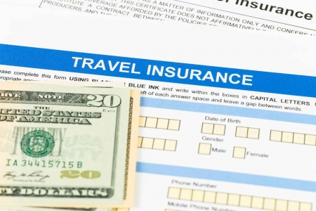 A travel insurance form with a $20 bill and a check.