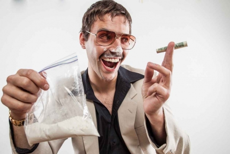 A man holding money in his hand with a large bag of cocaine in his other hand and cocaine on his nose.