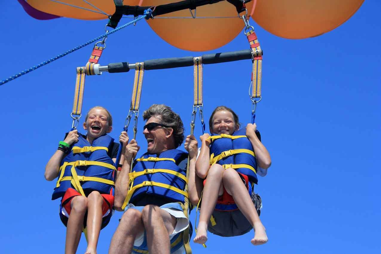A father and two twin daughters parasailing together.