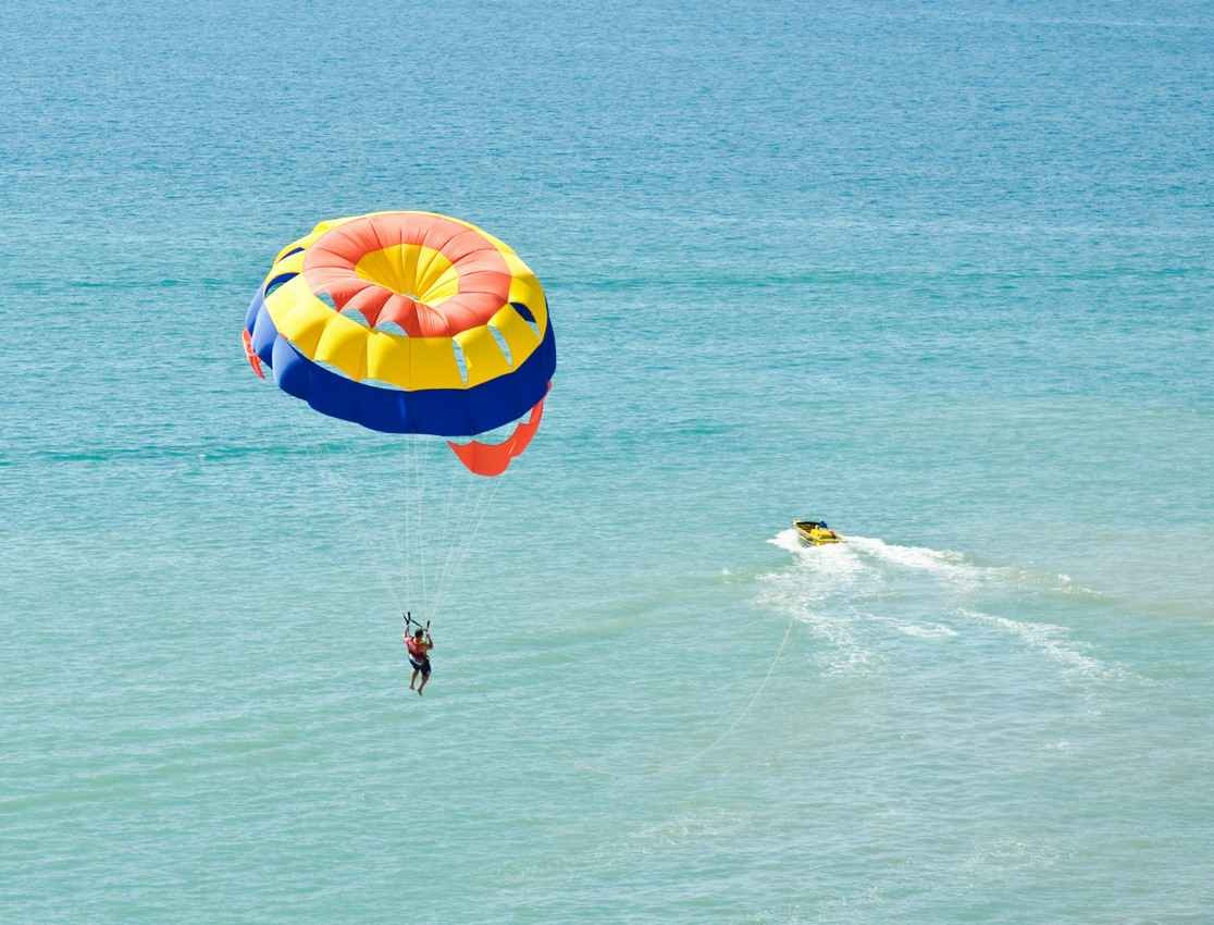 A man parasailing behind a yellow boat in Playa Del Carmen.