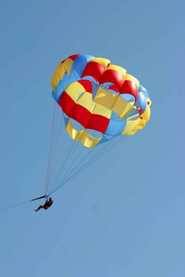A man parasailing over the beach.