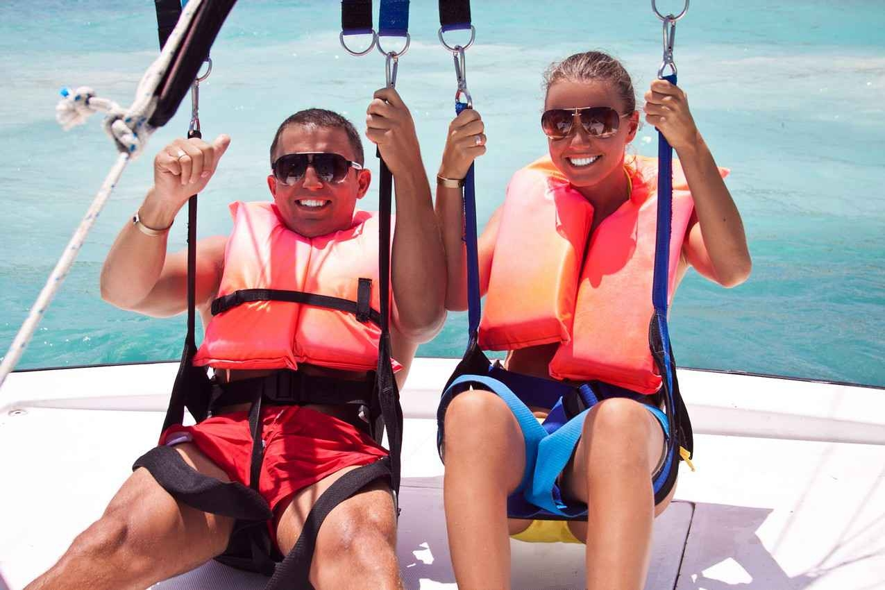 A newlywed couple preparing to go parasailing.