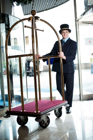A bellboy pushing a cart.