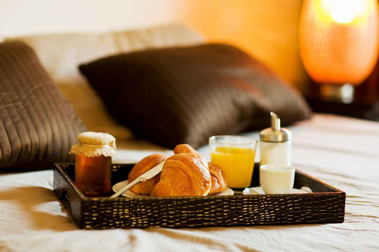 A delicious breakfast on a resort bed.
