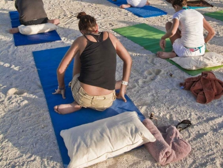 People doing yoga exercises on beach pads.
