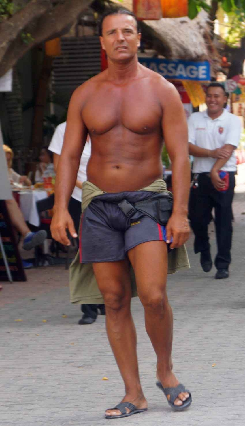 A darkly tanned and muscular man not wearing a shirt.
