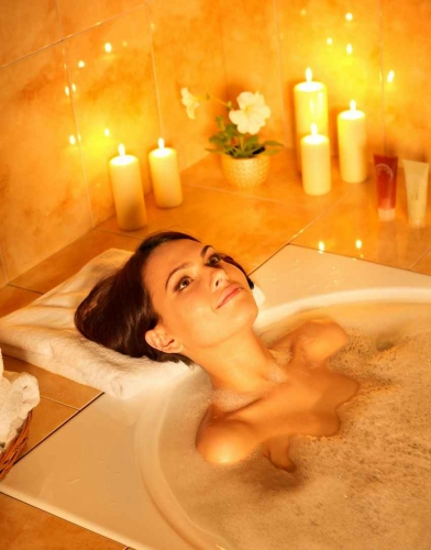 A woman sitting in a bubble bath Jacuzzi with candles all around her.