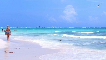 A beautiful beach in Playa Del Carmen with white sand and baby blue water.