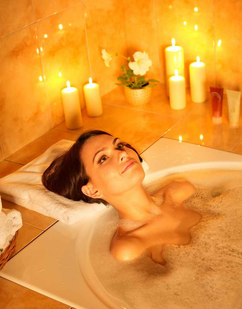 woman sitting in a bubble bath jacuzzi with candles all around her