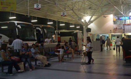 The bus station in Playa Del Carmen with several buses lined up outside.