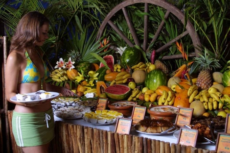 A variety of fresh fruits and desserts at a buffet.