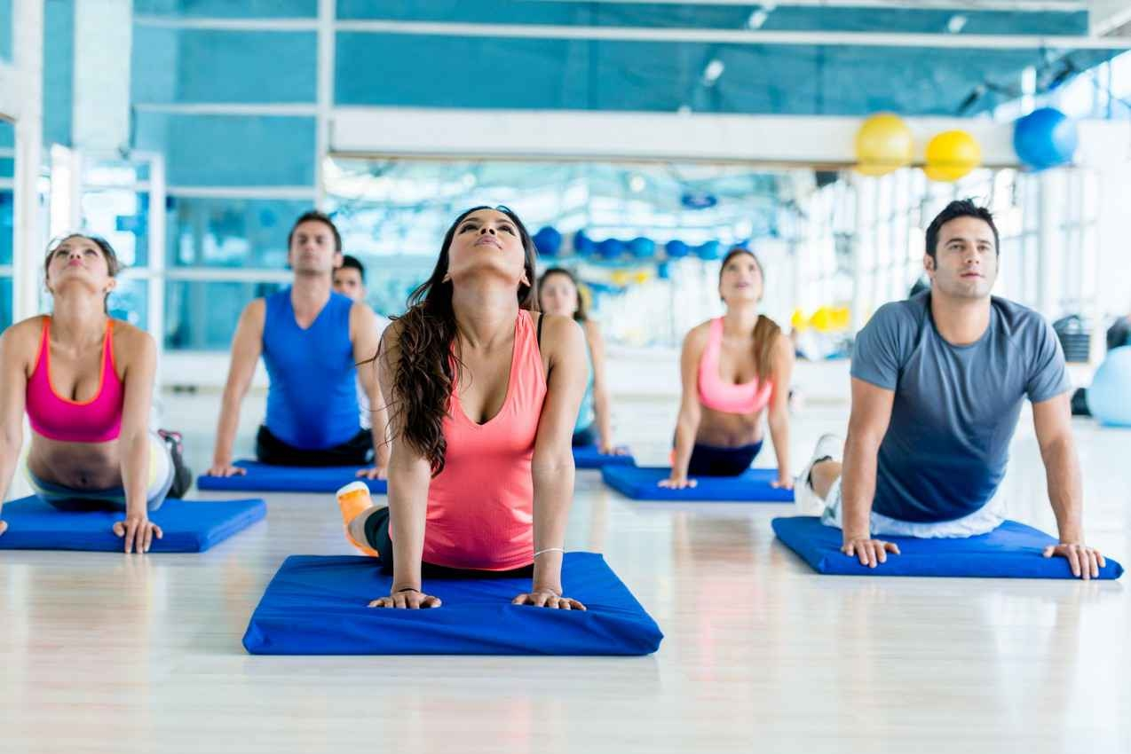 A mixed group of men and women doing yoga at a gym.