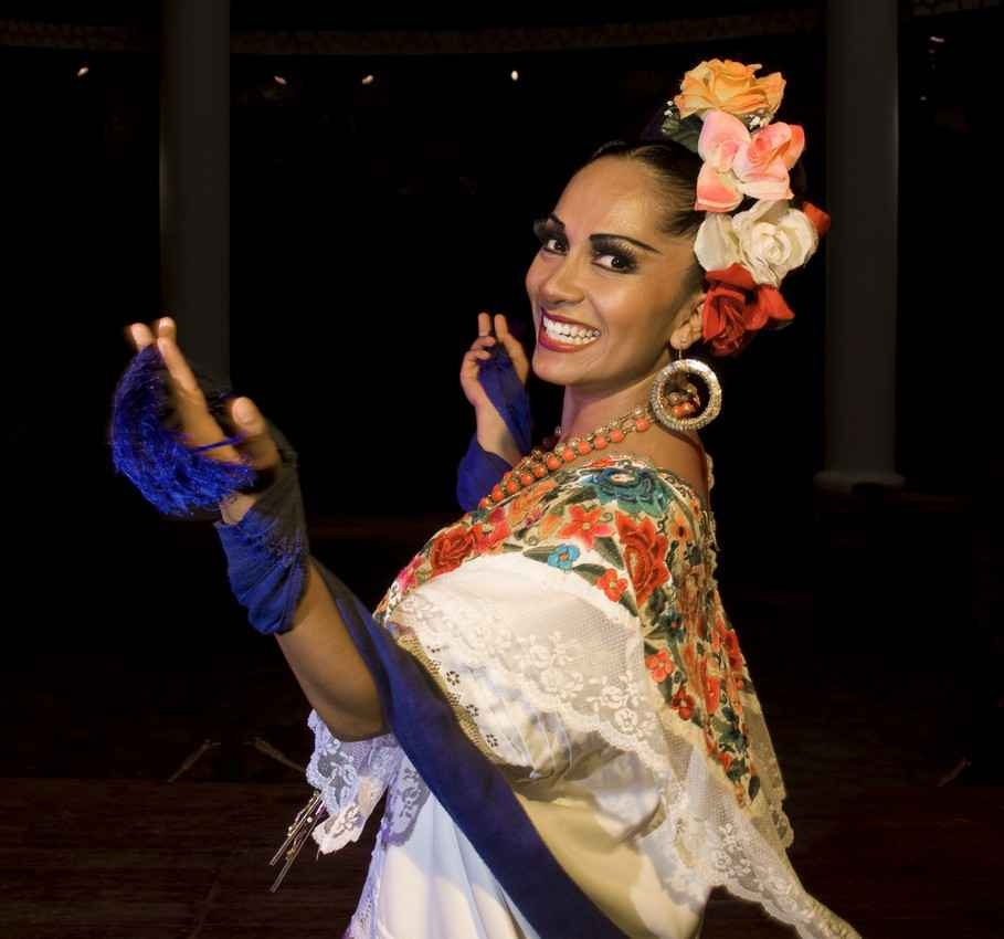 A Mexican traditional dancer who is dressed in traditional dance clothing.