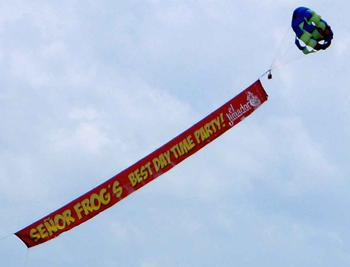 Senor Frogs airborne advertisement over the beach.