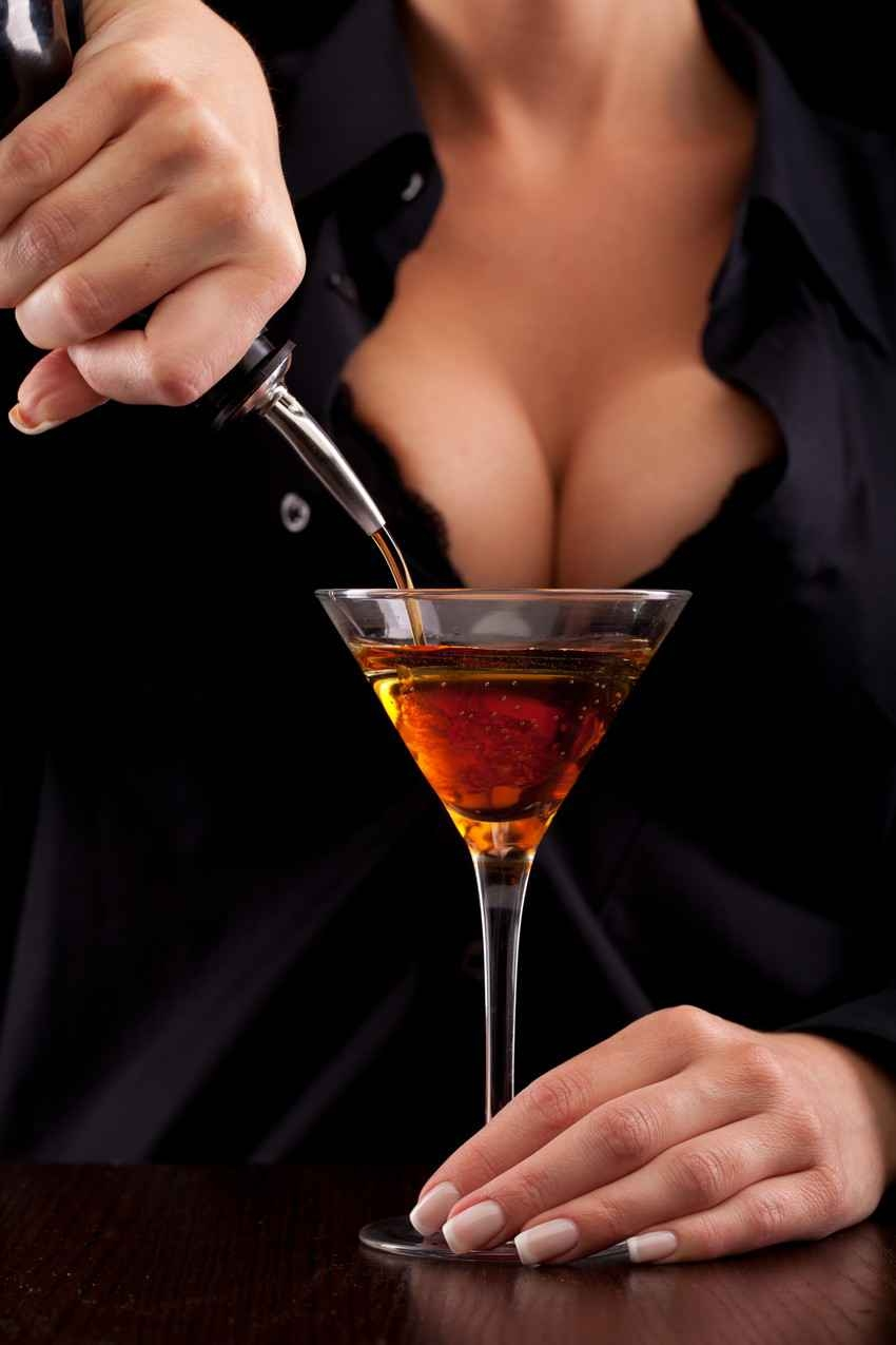 A sexy bartender with big boobs pouring a drink into a martini glass.