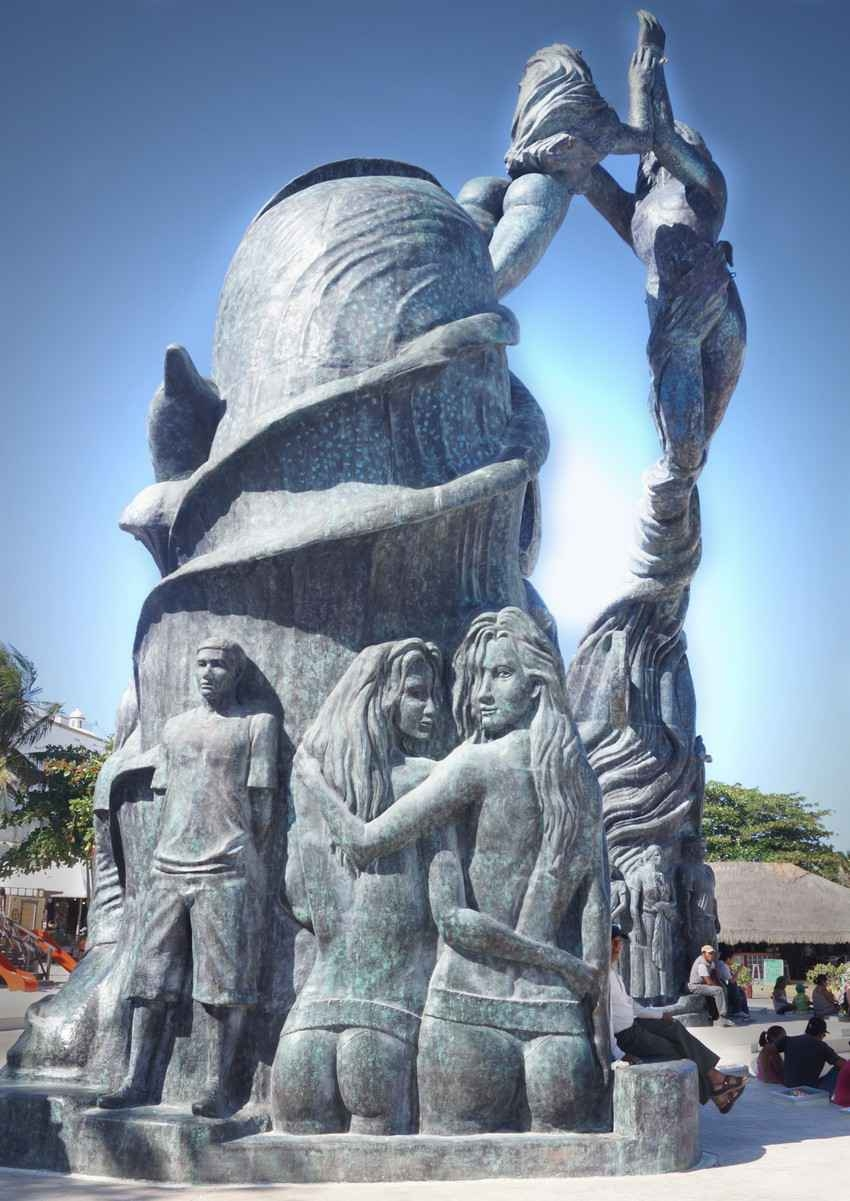 A side view of the statue that is on the beach in Playa Del Carmen featuring two women embracing.