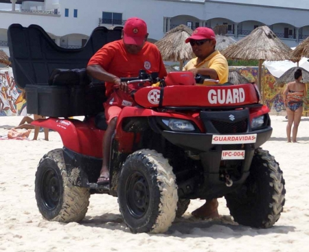 Two lifeguards riding an ATV on the beach in Playa Del Carmen.