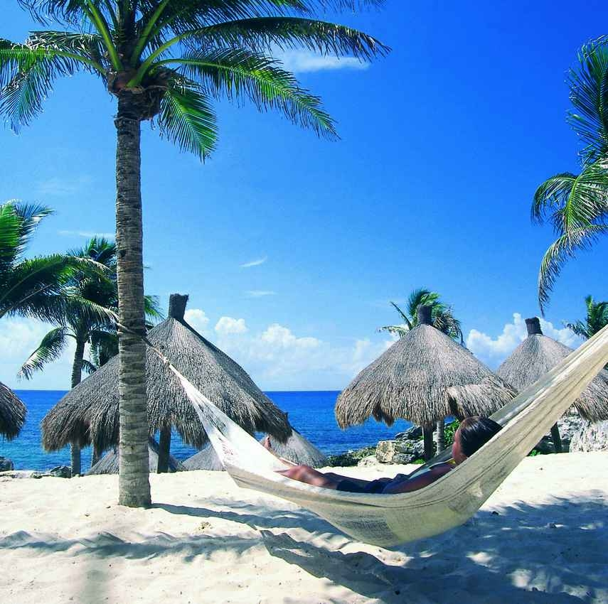 A woman lying in a beech hammock with several palapas behind her.