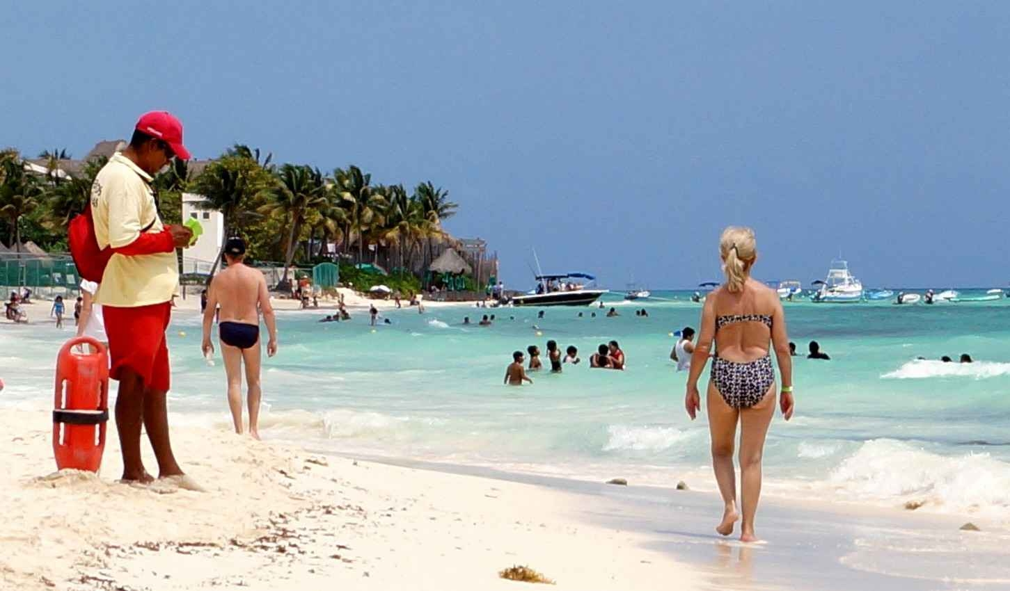 A middle-aged woman walked down the beach near a lifeguard in Playa Del Carmen.