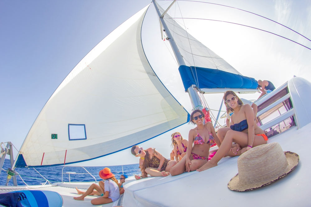 several-men-and-women-sitting-on-the-deck-of-a-booze-cruise-playa-del-carmen-catamaran