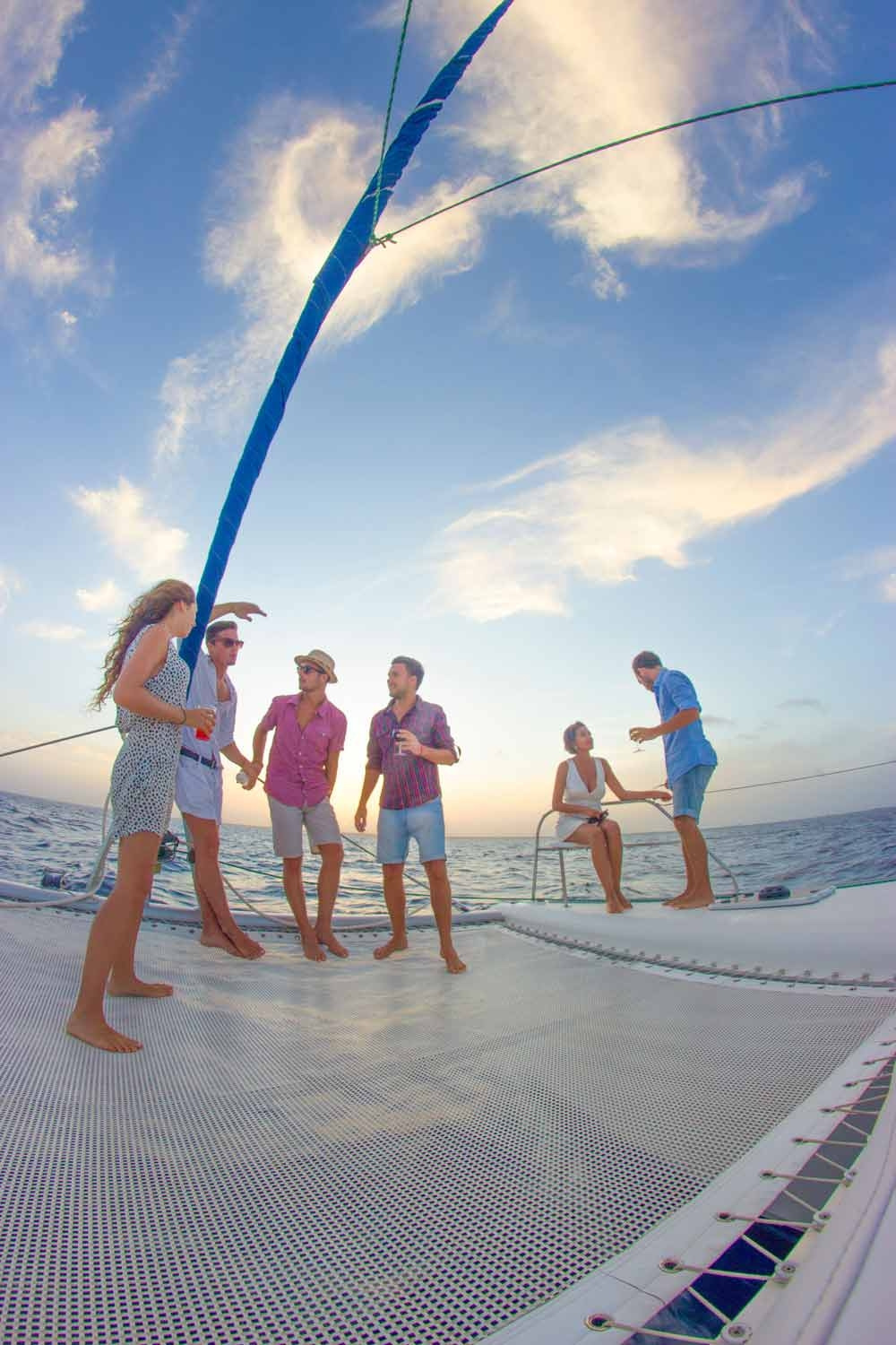 several-people-standing-on-the-deck-of-a-playa-del-carmen-booze-cruise-catamaran