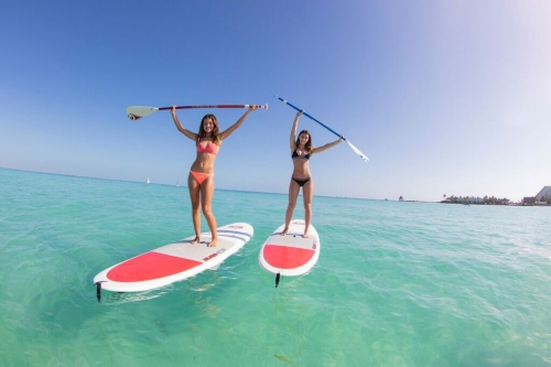 two-young-women-holding-their-paddles-above-their-heads-while-paddleboarding
