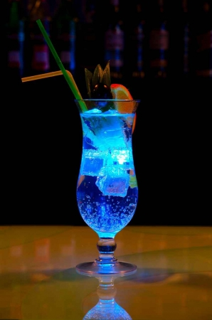 A brightly lit cocktail on the bar.